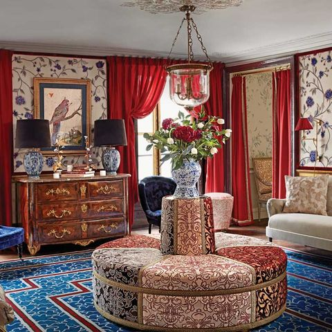 Upholstered banquette in room with red curtains