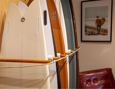 Rhythm shop interior surfboards lined up against the wall and framed photo of a surfer