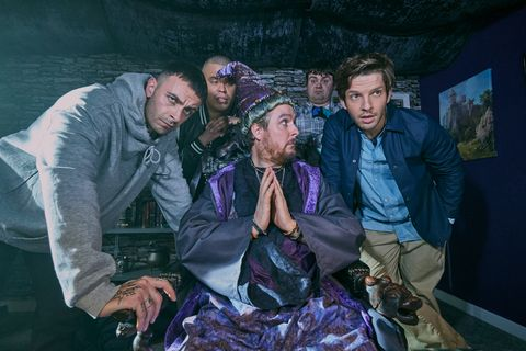 Still of the cast of Brassic sitting around a man dressed as a wizard