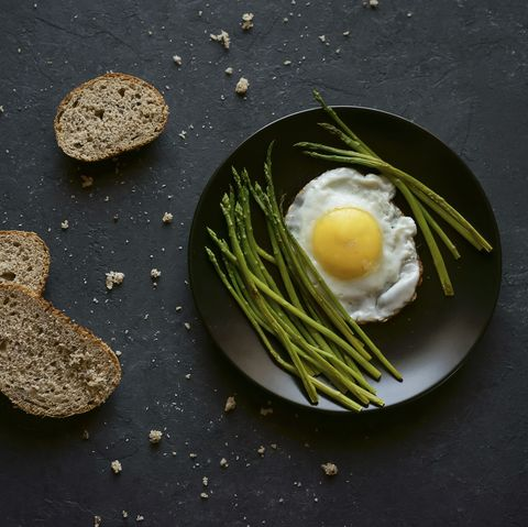 Bread and crumbs near plate with fried egg and asparagus