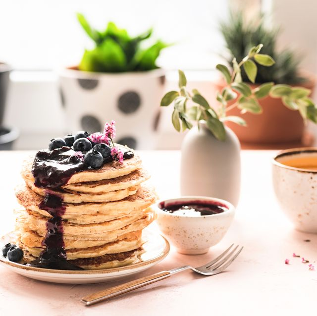 breakfast table with pancakes, blueberry jam and tea