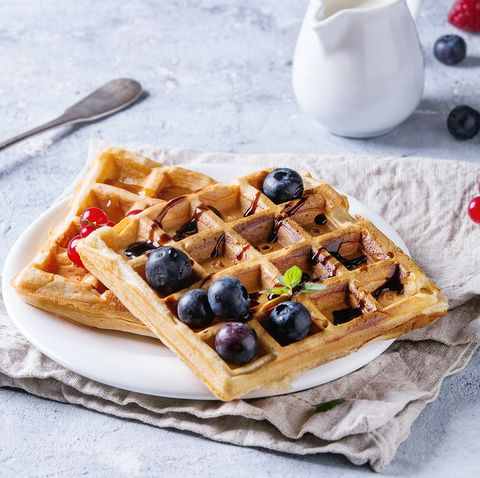 Breakfast with homemade square belgian waffles with fresh ripe berries blueberry, raspberry, red currant, balsamic sauce on white plate with jug of milk, textile napkin over gray texture background.