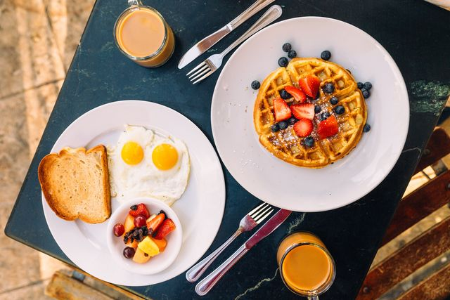 breakfast with sunny side up fried eggs, waffle and fruits