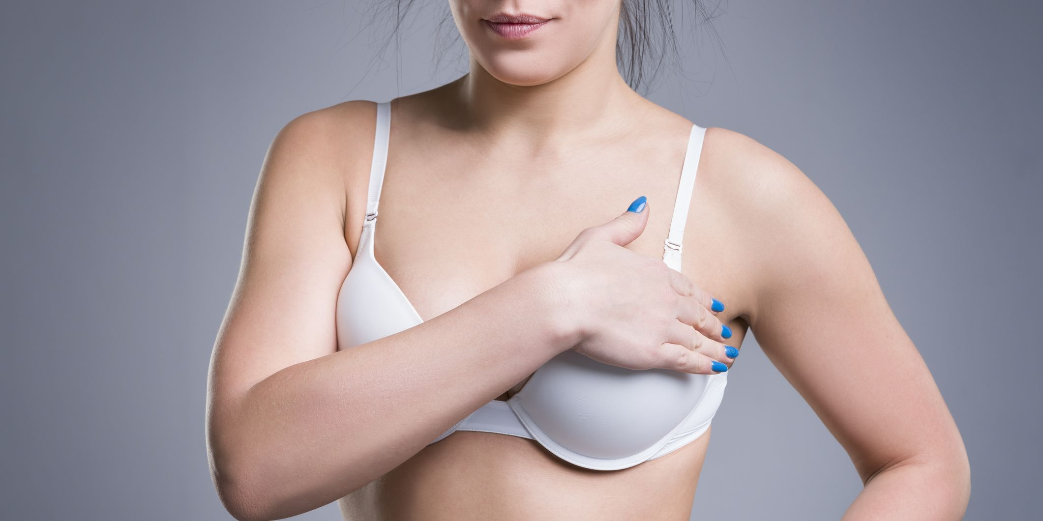 Woman in white push up bra on gray background, female breast
