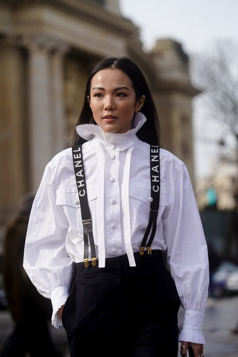 paris, france   march 03 yoyo cao wears a white shirt with ruffled collar, chanel straps, navy blue pants, outside chanel, during paris fashion week   womenswear fallwinter 20202021 on march 03, 2020 in paris, france photo by edward berthelotgetty images