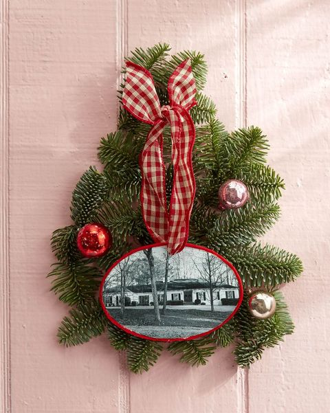 a home photo made into an ornament with greenery and small christmas balls surrounding it