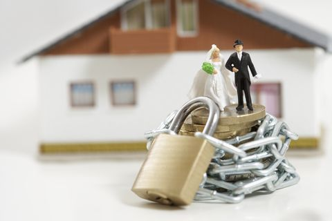 Bridal couple figurines on a stack of coins wrapped of a chain with padlock, miniature house in background
