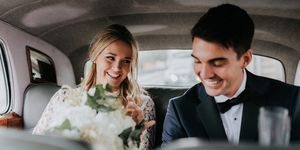 Bride and bridegroom in backseat of car