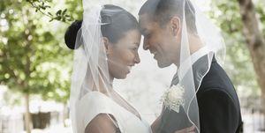 Bride and groom hugging under veil