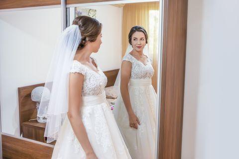 Bride in wedding dress looking in the mirror