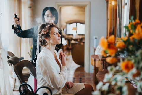 Bride preparing for wedding with hairstylist
