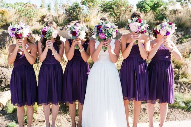 bride with bridesmaid standing with flower bouquets