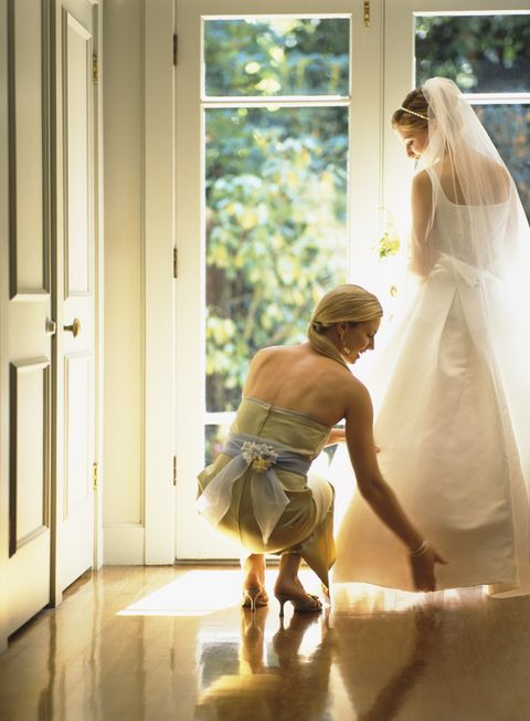Bridesmaid adjusting bride's dress beside French doors, rear view