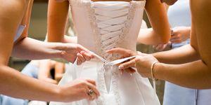 Bridesmaids help bride into her dress