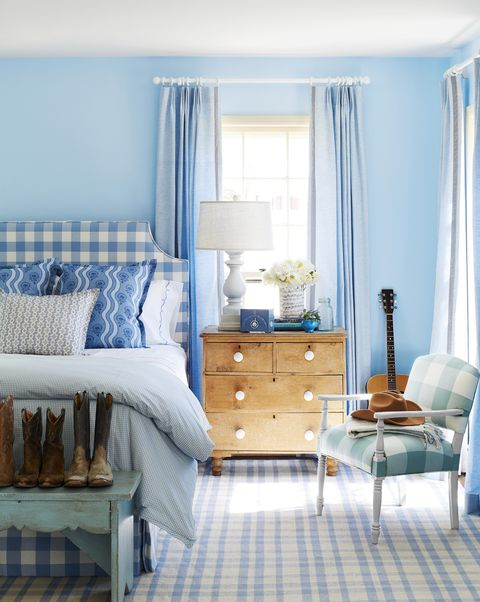 a blue and white bedroom with bright blue walls