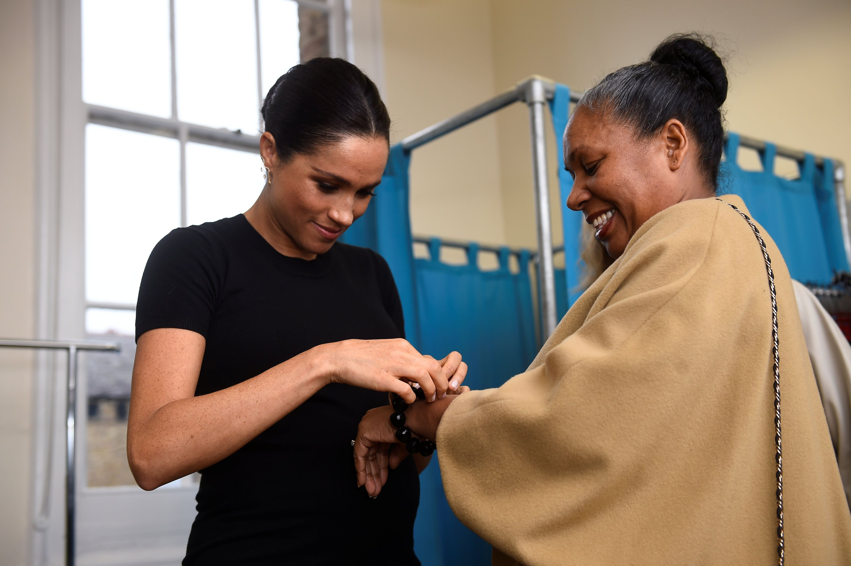 Meghan helps a woman at Smart Works try on a bracelet from the organization's collection of interview outfits.