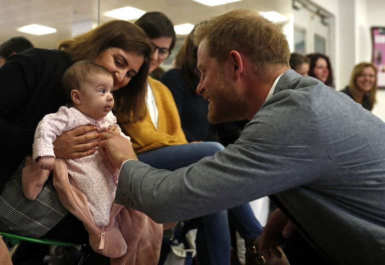Prince Harry playing with a baby during today's visit to the YMCA.