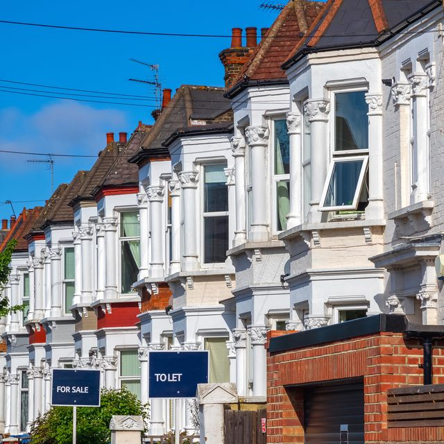 a row of typical british terraced houses around kensal rise in london with estate agent boards