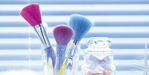 Vaso con brochas de maquillaje y tarro con bolitas de aceite