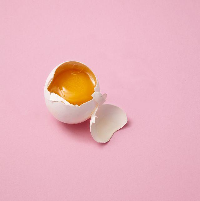 broken egg on pink background