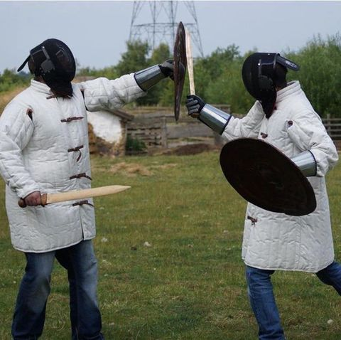 two archaeologists staging a sword fight