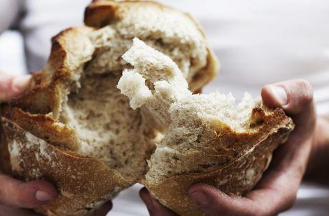 man breekt brood