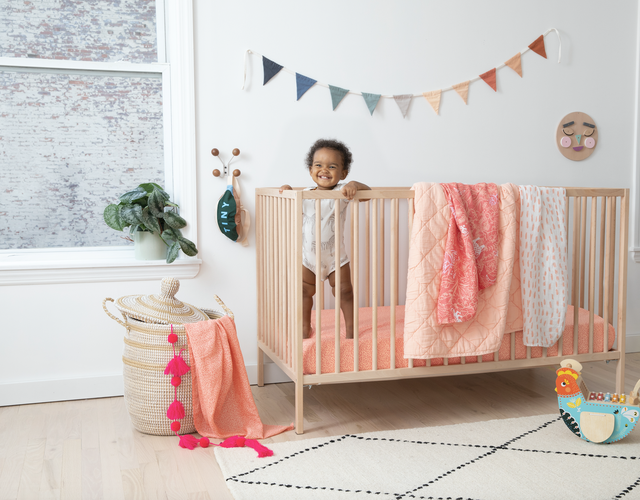 baby in crib with blush blankets