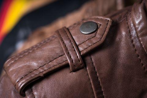Brown leather jacket shoulder metal clasp button. Macro leather shoulder detail