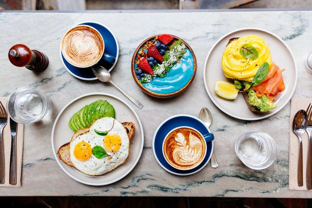 brunch at cafe with avocado toast, fried and scrambled egg, salmon, smoothie bowl and coffee
