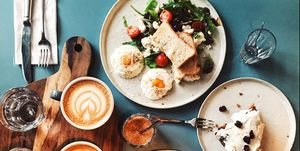 Brunch for two people with avocado toast, fried egg, salad, cappuccino and carrot cake served on the table, high angle view