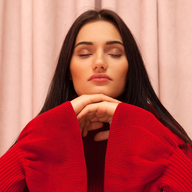 brunette woman wearing a red sweater closing her eyes