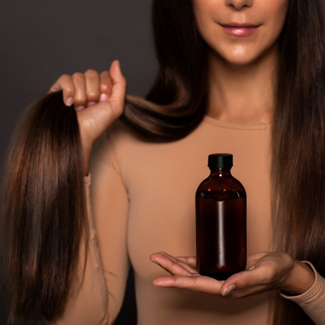 brunette girl with long straight and shiny hair  beauty skin woman holding her strong and healthy hair and oil or shampoo bottle over grey background cosmetic hair beauty salon concept