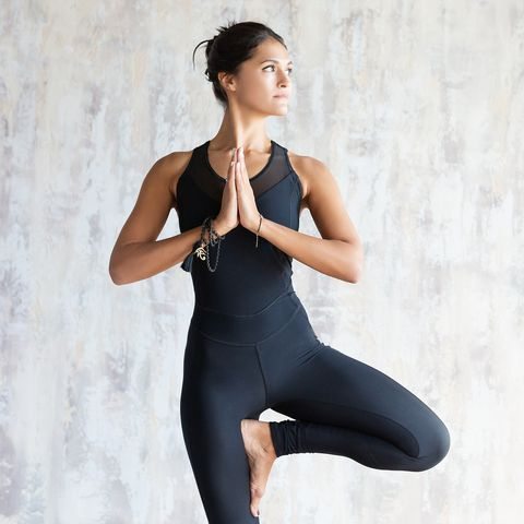 brunette woman yoga instructor doing vrikshasana