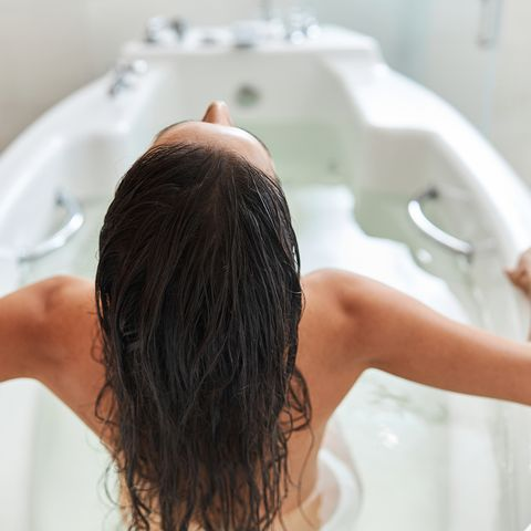 brunette young woman sitting in white bathtub