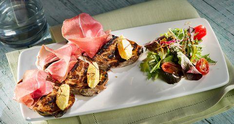 La ricetta della bruschetta al prosciutto crudo e caprino allo zafferano è l'antipasto estivo che stavate aspettando