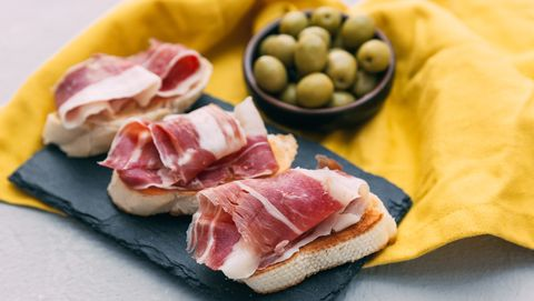 Bruschetta with prosciutto and a bowl of olives