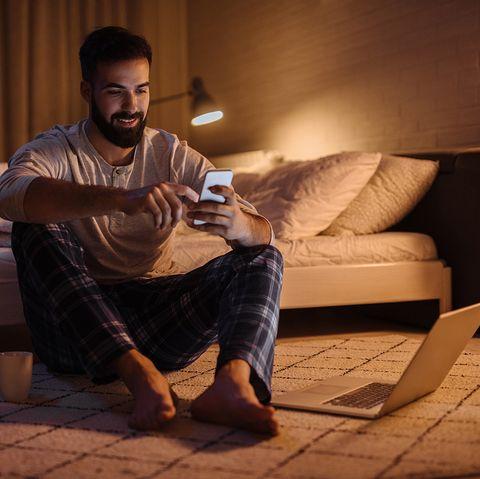 hombre joven sentado a los pies de la cama usando el móvil y el ordenador