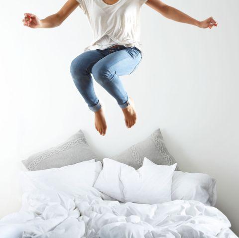 mujer saltando en la cama