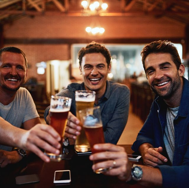 portrait of a group of young friends seated at a table together while enjoying a beer and celebrating with a celebratory toast inside a bar