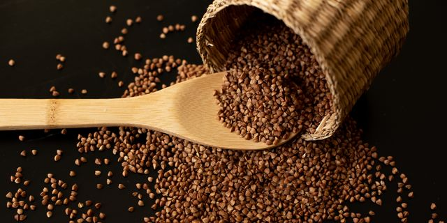 buckwheat seeds in wooden spoon on a brown wooden table