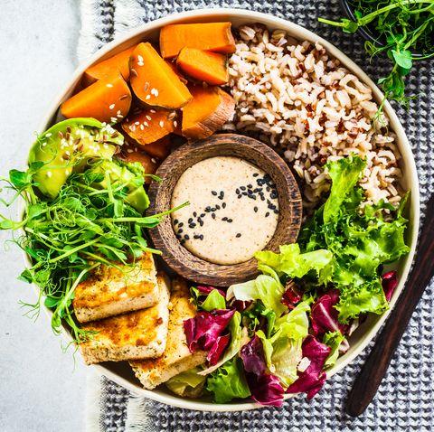 buddha bowl with tofu, avocado, rice, seedlings, sweet potato and tahini dressing