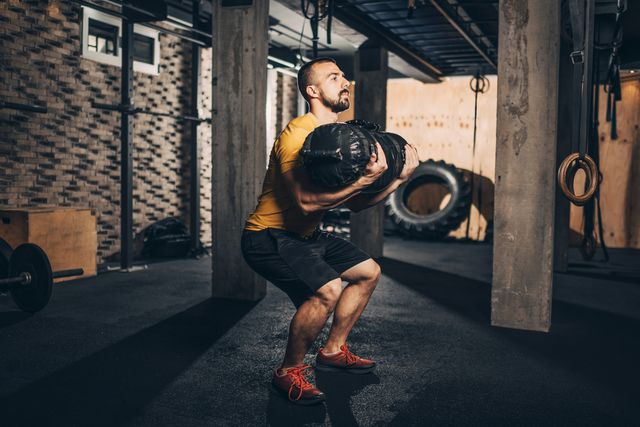 buff male athlete doing core bag squats exercise in a gym