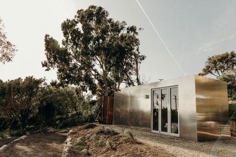 vista exterior de laMinicasa Buhaus, hecha con un contenedor metalizado y situada en una zona de campo en Malibu.