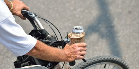 A cyclist with a beer in his hand.