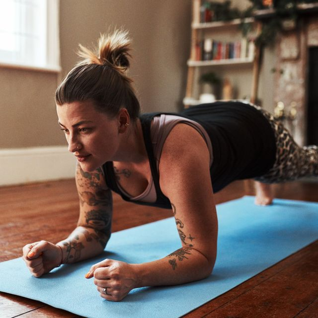 woman performing plank position workout at home