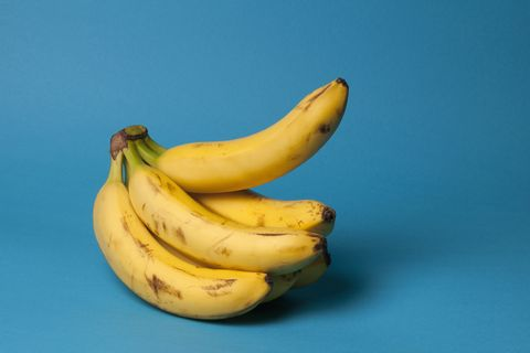 A bunch of bananas with one banana sticking up, suggestive of an erection