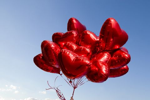 a bunch of red heart shaped balloons