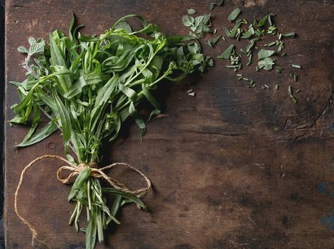 Bundle of fresh and cutting Italian herbs rosemary, oregano and sage over old dark wooden and black ornate background. Top view with copy space