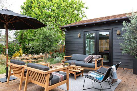 bungalow de madera en color negro con zona de asientos en la terraza