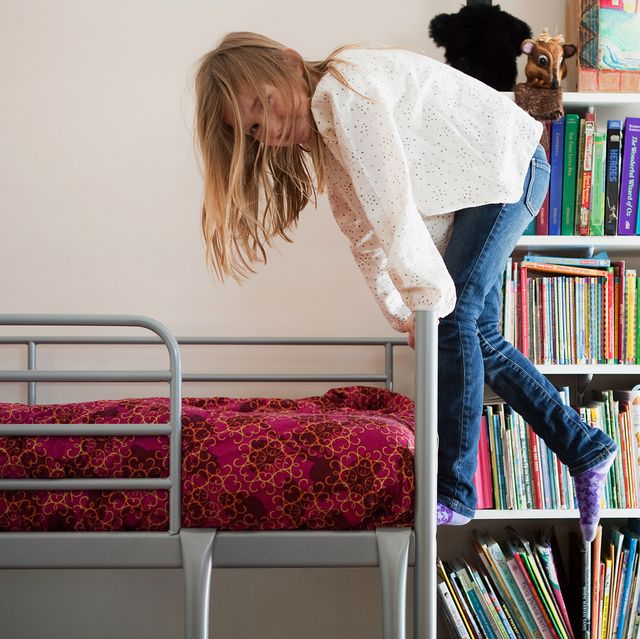 girl hanging off o bunk bed